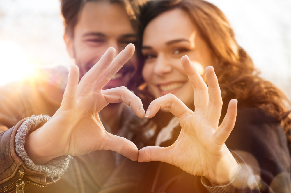 Paar formt Herz in Fruchtbarkeits-Phase der Frau